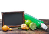 Bottles of juice from citrus fruits and blackboard — Stok fotoğraf