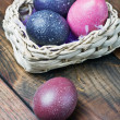 Easter eggs in brown a basket on a wooden table — Stock Photo