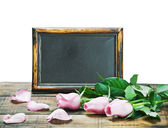 Black board and pink roses — Stock Photo