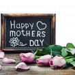 Stock Photo: Pink roses and congratulations on Mother's Day on white