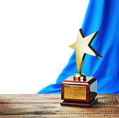 Star award wooden table and on the background of blue curtain — Stock Photo