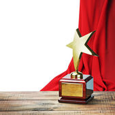 Star award wooden table and on the background of red curtain — Stock Photo