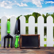 Garden tools and equipment and a white fence - Stock Photo