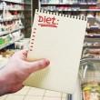 Hand holds a notebook with diet plan - Stock Photo