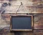 Blackboard on wooden background — Stock Photo