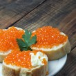Red caviar on slices of baguette — Stock Photo #23343566