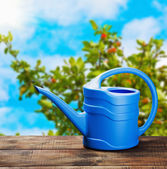 Blue watering can on the table — Stock Photo