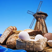 Fresh bread on the background of the wooden mill — Stock Photo