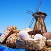 木製ミルの背景に焼きたてのパン — ストック写真