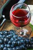 Glass of red wine with bottle — Stock Photo