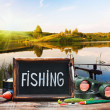 Fishing tackle and a blackboard — Stock Photo