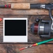 Fishing tackle and photo frame on wooden table - Stock Photo