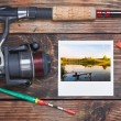 Fishing tackle and a photo of successful fishing — Stock Photo #25345049