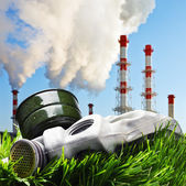 Gas mask on a green grass on a background of smoking chimneys — Stock Photo