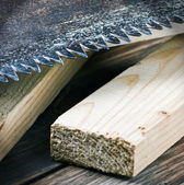 Teeth of an old metal saws and sawn timber — Stock Photo