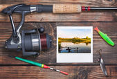 Fishing tackle and a photo of successful fishing — Stock Photo