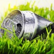 Crumpled aluminum can on a green grass — Stock Photo