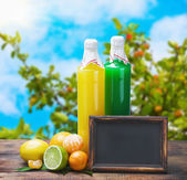 Bottles of juice from citrus fruits and blackboard — Stock Photo