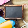 Stock Photo: Blackboard and beach gear lie on sand