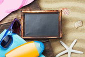 Blackboard and beach gear lie on the sand — Stock Photo