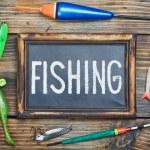Fishing gear and blackboard — Stock Photo #26553937