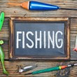 Fishing gear and blackboard — Stock Photo #26553937