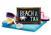 Blackboard with the word beach and tan — Stock Photo