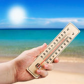 Thermometer in hand shows the intense heat — Stock Photo