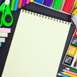 Notepad and various school supplies — Stock Photo