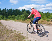 Mountain bike teenager with blue sky — Stock Photo
