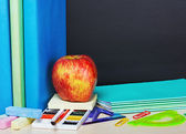 Ripe apple and school supplies — Stock Photo