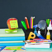 Back to school supplies and board — Stock Photo