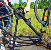 Repairing a bicycle in a field — Stock Photo