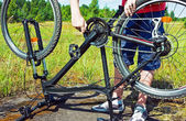 Man's arms fixing a bike in a grassy field. — Stock Photo