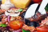 Cutter snijdt een verse pizza met champignons — Stockfoto