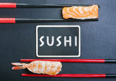 Chopsticks and two sushi with salmon and shrimp — Stock Photo