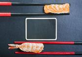 Palillos y dos sushi con salmón y camarones en un negro backg — Foto de Stock