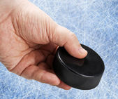Hand holding a hockey puck — Stock Photo