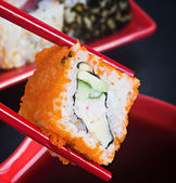 Chopsticks hold roll — Stock Photo