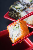Chopsticks hold fresh roll — Stock Photo