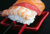 Fresh sushi served in a red plate with black stripes — Stock Photo
