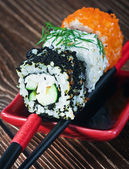 Fresh roll served in a red plate with black stripes — Stock Photo