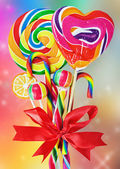 Colored sweets with red ribbon bow — Stock Photo