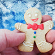 Smiling gingerbread man in the hand — Stock Photo