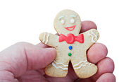 Smiling gingerbread men in a hand — Stock Photo