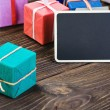 Gifts in the box and blackboard — Stock Photo