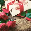 Stock Photo: Red roses and holiday gift on a wooden table