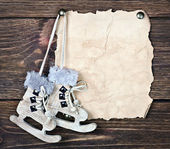 Christmas wooden toy figure skates and a piece of old paper — Stock Photo