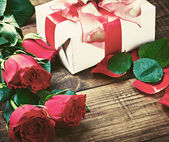 Red roses and holiday gift on a wooden table — Stock Photo