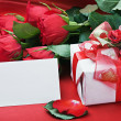 Red roses and white card — Stok fotoğraf